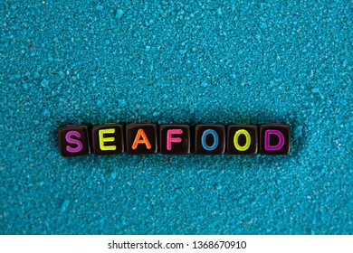 The word seafood is made up of colored letters on black cubes on blue sand
