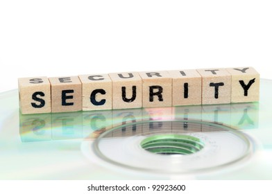 The word security written in wooden letters standing on a computer-CD
