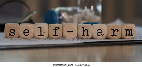 Word  SELF-HARM   composed of wooden dices. Pills, documents and a pen in the background. Closeup