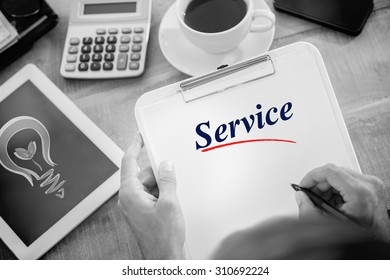 The word service and man writing on clipboard on working desk against green energy