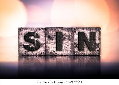 "The word ""SIN"" written in vintage ink stained letterpress type."