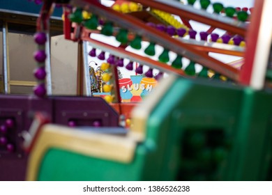 The word Slush can be seen in the background through unlit lights on a fairground early in the morning. Selective focus on the word Slush, with bokeh present in the foreground.