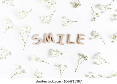 Word Smile made of wooden letters. Floral pattern made of white gypsophila on a white background