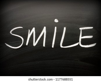 The word Smile written by hand in white chalk on a blackboard as a reminder. A vignette has been added for effect