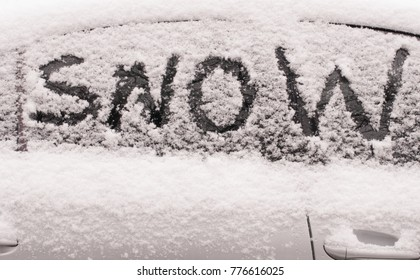 """The word """"snow"""" traced into snow on window of white car"""
