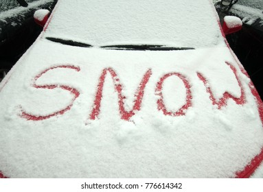 """The word """"snow"""" traced in snow on hood of red car"""