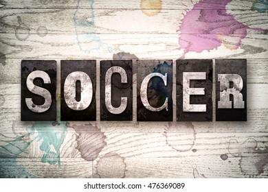 "The word ""SOCCER"" written in vintage, dirty metal letterpress type on a whitewashed wooden background with ink and paint stains."