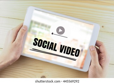 word social video on white tablet in hand wood background,content marketing concept