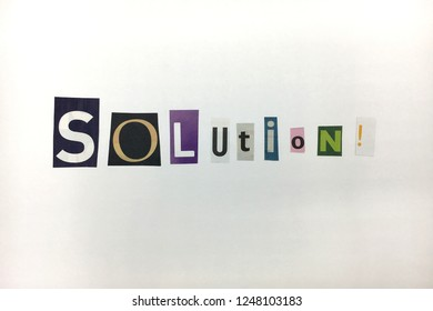 """The word """"Solution""""in cut out letters blackmail style in white background"""
