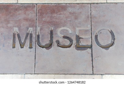 Word ¨museum´ in Spanish engraved in stone pavement on the ground. There is water on half of the letters.