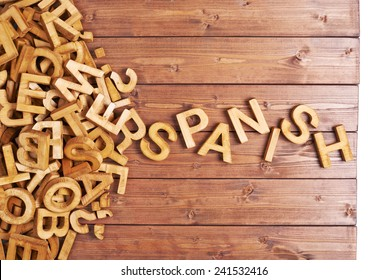 Word spanish made with block wooden letters next to a pile of other letters over the wooden board surface composition