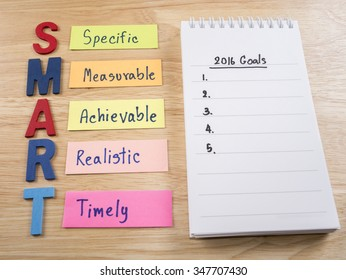Word spell SMART Goals and 2016 Goals in notebook on wood background