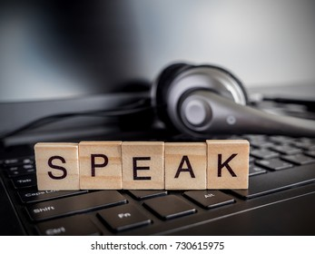 "Word spell ""Speak"" over laptop keyboard and headset (Communication concept)"