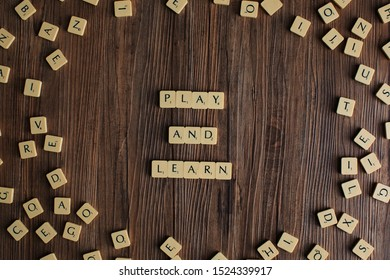 The word 'Play and Learn' spelled out with scrabble, isolated on wooden background, presentation background, play and learn concept, education concept, early childhood education concept - Image