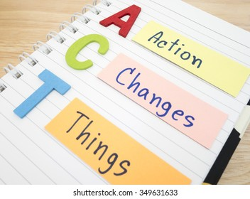 """Word spelling """"Action Changes Things"""" on white notebook with wood background (Business concept)"""