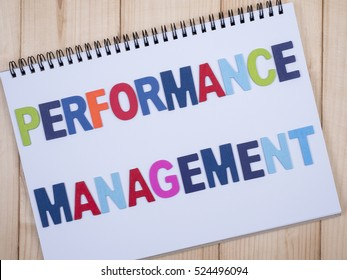 Word spelling Performance Management on white notebook with wood background, top view