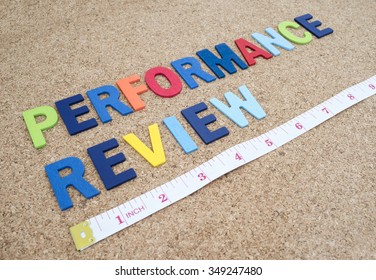 "Word spelling ""Performance Review"" and measuring tape on cork board"