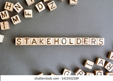 the word stakeholder wooden cubes with burnt letters, business development in favor of shareholders gray background top view, scattered cubes around random letters