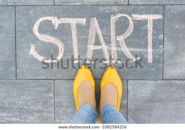 Word start on the asphalt and feet woman