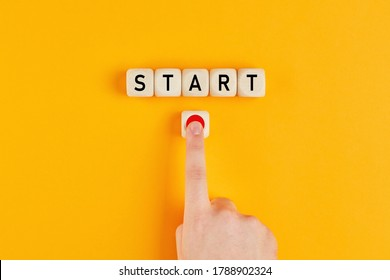 The word start on wooden cubes with a male hand pressing the start button. To make a new start in life, business, education or career concept.