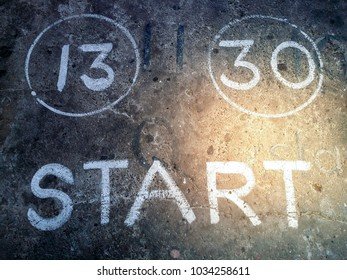 The word START painted in white along with some numbers on a rustic, worn out concrete wall with golden sunlight spot on it as creative background
