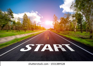 The word start written on highway road in the middle of empty asphalt road at  beautiful blue sky.