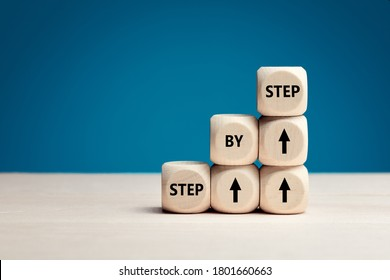 The word step by step on wooden cubes. Achievement or progress in business career.