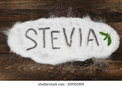 the word stevia written in stevia powder on wooden background