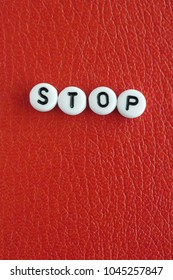 Word STOP made of round letters isolated on red leather background
