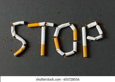 Das Wort wird mit Zigaretten auf schwarzem Hintergrund geschrieben