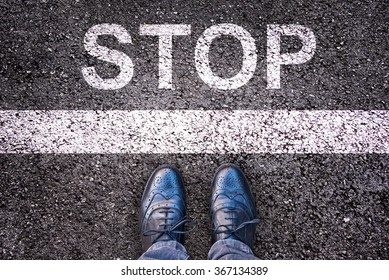 Word Stop written on an asphalt road with legs and shoes