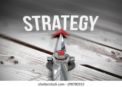 The word strategy and compass against digitally generated grey wooden planks