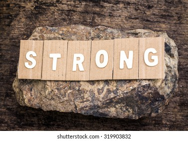 "the word "" strong "" design by white letterpress  over the stone on wooden background"