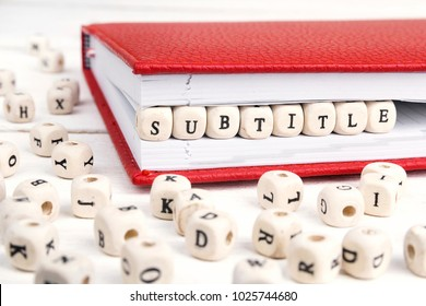 Word Subtitle written in wooden blocks in red notebook on white wooden table. Wooden abc.