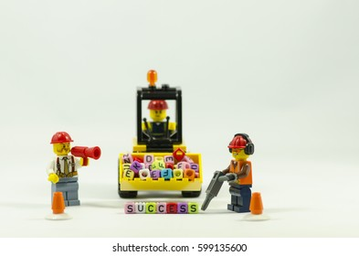 word success spell using colorful alphabet beads with lego miniature worker.Lego minifigures are manufactured by The Lego Group. concept image focus on word success.studio shot.