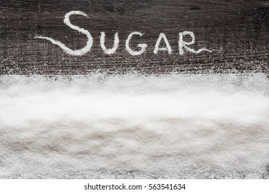 Word sugar created from sugar on the wooden background in the kitchen. Sweet meal.