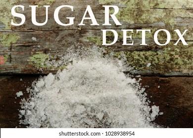 Word SUGAR DETOX with white sugar on wooden background