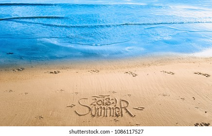 "The word ""Summer 2018"" is written in the sand. The inscription is made by hand. Blue sea wave."