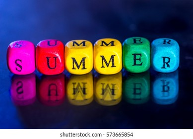 """Word """"summer"""" of the colored wooden cubes isolated on dark background."""