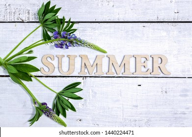 Word summer on light wooden background. Flat lay