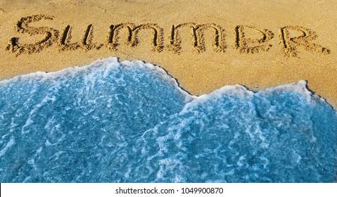 The word Summer written on a sand. Summertime.