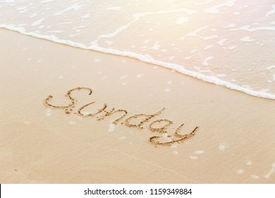 The word Sunday written in sand beach with sunlight reflex and wave in background, bird eye view. Outdoor picture in summer season. Day, weekend, travel and relaxation concepts.