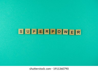 Word Superpower. The phrase is laid out in wooden letters. Top view. Motivation. Blue background. Copy space.