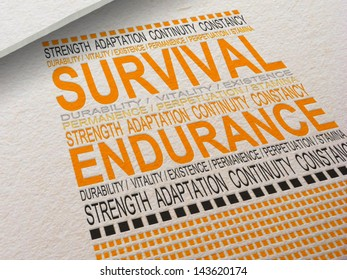 The word Survival letter pressed into paper with associated words around it.