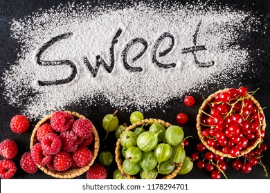 The word sweet is written on a dark background with the help of powdered sugar next to berries. raspberries, gooseberries, red currants. Top view, flat lay. Sweet, stylish desserts concept