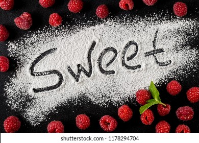 The word sweet is written on a dark background with the help of powdered sugar next to raspberry berries. Top view, flat lay. Sweet, stylish desserts concept