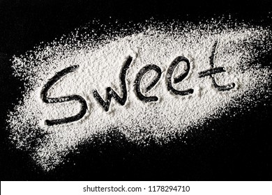 The word sweet is written on dark background with the help of powdered sugar. Sweet, stylish desserts concept. Top view, flat lay