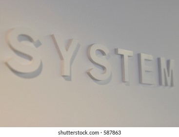 """The word """"system"""" embossed on a white wall, partially blurred"""