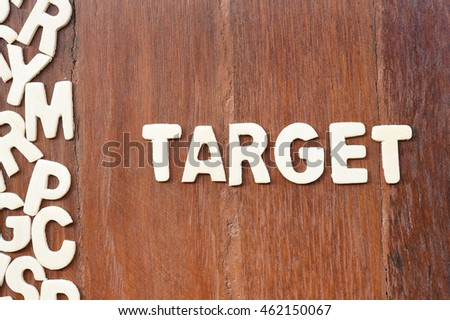 word target made with block wooden letters next to a pile of other letters over the