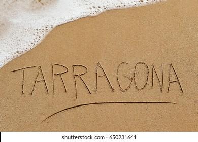 the word Tarragona written in the sand of a beach in Tarragona, Spain